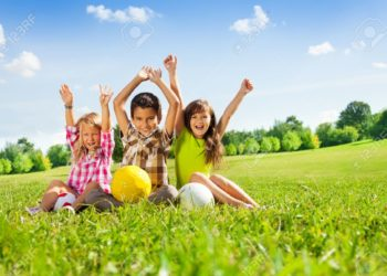 24234030-portrait-of-three-happy-kids-boy-and-girls-sitting-in-the-grass-in-park-with-lifted-hands-and-holdin